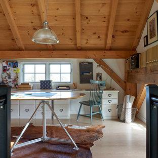 Foto på ett stort lantligt hobbyrum, med vita väggar, ljust trägolv och ett inbyggt skrivbord