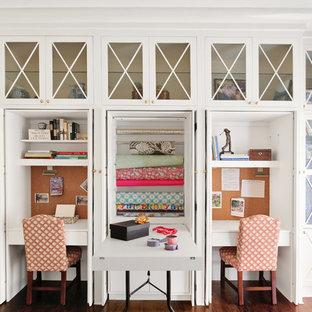 Bild på ett vintage hobbyrum, med vita väggar, mellanmörkt trägolv, ett inbyggt skrivbord och brunt golv
