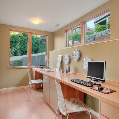 Example of a trendy built-in desk medium tone wood floor home office design in Seattle