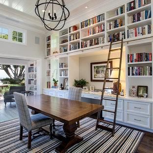 Inspiration för ett vintage arbetsrum, med ett bibliotek, vita väggar, mörkt trägolv, ett fristående skrivbord och brunt golv