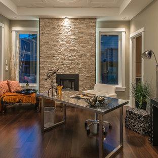 Стильный дизайн: кабинет в современном стиле с серыми стенами, темным паркетным полом, стандартным камином, фасадом камина из камня и отдельно стоящим рабочим столом - последний тренд