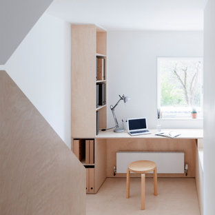 Design ideas for a modern home office in London with white walls, a built-in desk and beige floors.