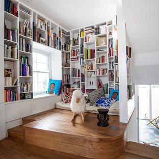 Ispirazione per un piccolo studio minimal con libreria, pareti bianche, nessun camino e pavimento in legno massello medio