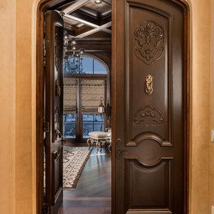 フェニックスの広いラスティックスタイルのおしゃれなホームオフィス・書斎 (ライブラリー、茶色い壁、無垢フローリング、コーナー設置型暖炉、石材の暖炉まわり、自立型机、茶色い床) の写真