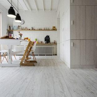 Bild på ett stort funkis hobbyrum, med vita väggar, linoleumgolv, ett fristående skrivbord och vitt golv