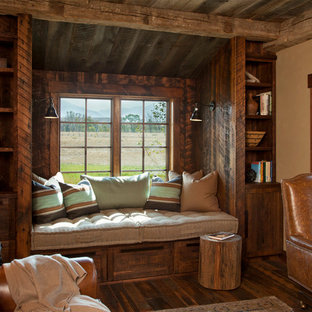 Mid-sized mountain style dark wood floor home office library photo in Other with beige walls