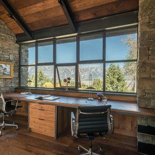 Modelo de despacho rústico, sin chimenea, con suelo de madera en tonos medios y escritorio empotrado
