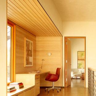 ロサンゼルスのコンテンポラリースタイルのおしゃれなホームオフィス・書斎 (ベージュの壁、無垢フローリング、造り付け机、ベージュの床) の写真