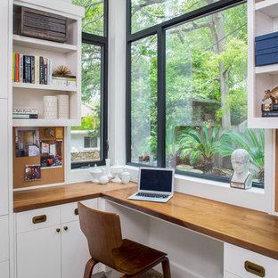 Ispirazione per uno studio tradizionale con pareti bianche, pavimento in cemento e scrivania incassata