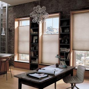 Großes Industrial Arbeitszimmer mit hellem Holzboden, freistehendem Schreibtisch, Arbeitsplatz, roter Wandfarbe und braunem Boden in New York