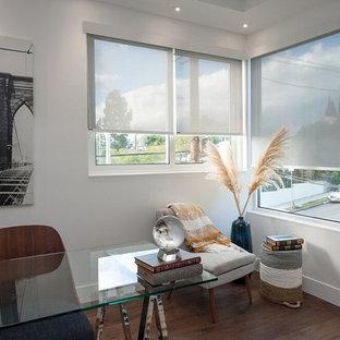 Ejemplo de despacho retro, de tamaño medio, sin chimenea, con paredes grises, suelo de madera oscura, escritorio independiente y suelo marrón