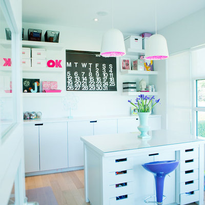 Inspiration for a contemporary freestanding desk light wood floor craft room remodel in Calgary with white walls