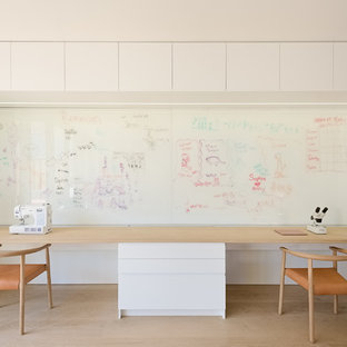 Example of a mid-sized minimalist built-in desk light wood floor and beige floor study room design in San Francisco with white walls