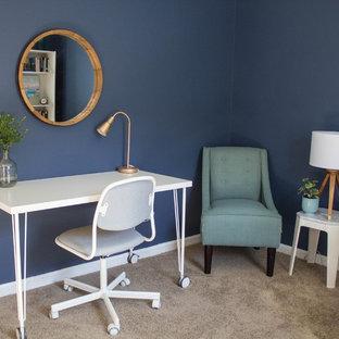 Inspiration för ett litet funkis hemmabibliotek, med blå väggar, heltäckningsmatta, ett fristående skrivbord och beiget golv