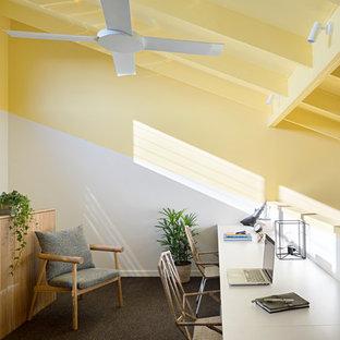 Diseño de despacho actual con paredes amarillas, moqueta, escritorio empotrado y suelo gris