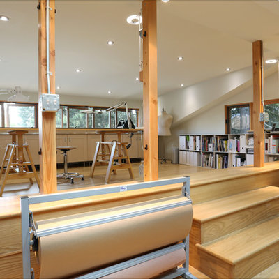 Trendy freestanding desk medium tone wood floor home studio photo in Portland with white walls
