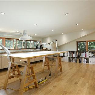 Ispirazione per un atelier contemporaneo con pareti bianche, scrivania autoportante e parquet chiaro