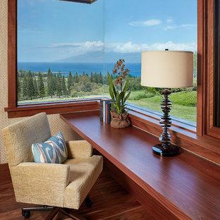 Idéer för att renovera ett litet tropiskt hemmabibliotek, med ett inbyggt skrivbord och mellanmörkt trägolv