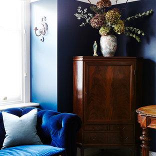 ロンドンの大きいトラディショナルスタイルのおしゃれな書斎 (青い壁、塗装フローリング、薪ストーブ、レンガの暖炉まわり、自立型机、白い床) の写真