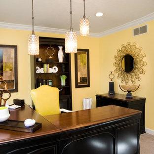 Immagine di un grande ufficio tradizionale con pareti gialle, moquette, nessun camino e scrivania autoportante