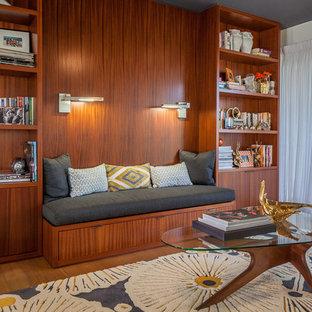 Exemple d'un bureau tendance avec un mur orange et un sol marron.