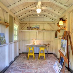 This is an example of a rustic home studio in Los Angeles with brick flooring.