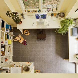 Ispirazione per uno studio chic di medie dimensioni con pareti gialle, pavimento in gres porcellanato, scrivania incassata, nessun camino e pavimento grigio