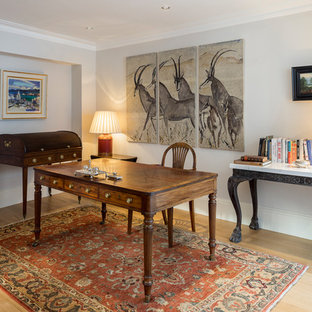 Inspiration for a traditional home office and library in London with grey walls, a freestanding desk, light hardwood flooring and beige floors.