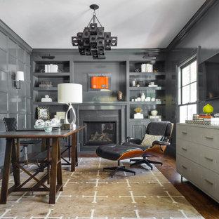 Mittelgroßes Klassisches Lesezimmer mit grauer Wandfarbe, dunklem Holzboden, Kamin, Kaminumrandung aus Stein, freistehendem Schreibtisch und braunem Boden in San Francisco