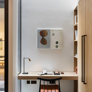 Inspiration for a small contemporary home office and library in London with white walls, a built-in desk and beige floors.