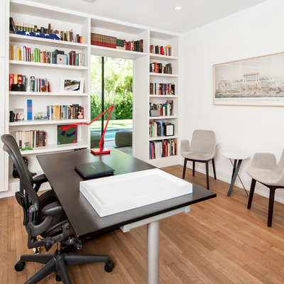 Home office - contemporary freestanding desk medium tone wood floor home office idea in Austin with white walls