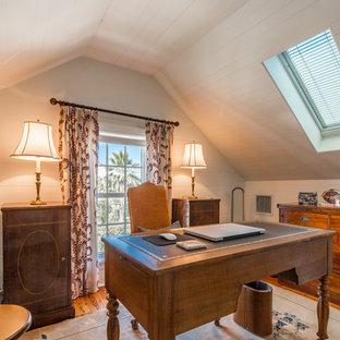 Exempel på ett klassiskt hemmabibliotek, med vita väggar, mellanmörkt trägolv, ett fristående skrivbord och orange golv