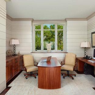 Foto på ett maritimt hemmabibliotek, med vita väggar, mörkt trägolv och ett inbyggt skrivbord