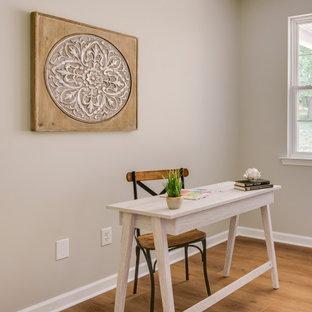 Ejemplo de despacho actual, pequeño, con suelo vinílico, escritorio independiente, suelo amarillo y paredes beige