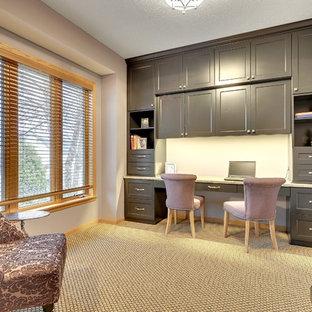 Foto de despacho clásico renovado con paredes púrpuras, moqueta y escritorio empotrado