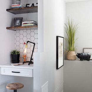 Immagine di un piccolo studio country con pareti bianche, pavimento in laminato, nessun camino e scrivania incassata
