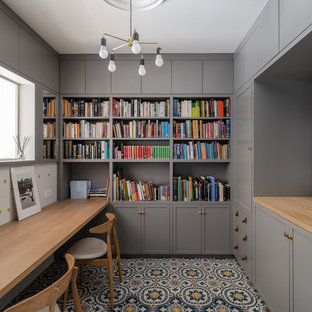 Inspiration for a traditional home office and library in London with a built-in desk and multi-coloured floors.