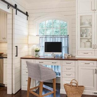 Elegant built-in desk dark wood floor home office photo in Charlotte with white walls