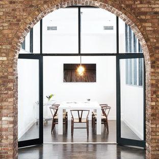 Пример оригинального дизайна: домашняя мастерская в стиле модернизм с белыми стенами, темным паркетным полом, отдельно стоящим рабочим столом, коричневым полом и кирпичными стенами
