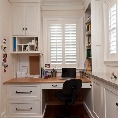Inspiration for a timeless built-in desk dark wood floor home office remodel in Other with white walls