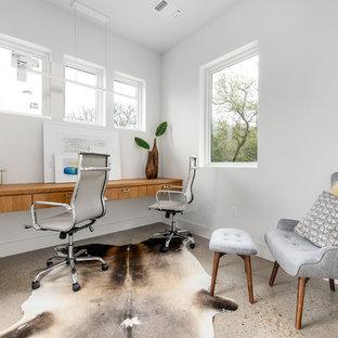 オースティンの中サイズのミッドセンチュリースタイルのおしゃれなホームオフィス・仕事部屋 (白い壁、コンクリートの床、暖炉なし、造り付け机、ベージュの床) の写真