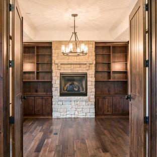 他の地域の大きいラスティックスタイルのおしゃれなホームオフィス・書斎 (ベージュの壁、無垢フローリング、標準型暖炉、石材の暖炉まわり、ライブラリー、茶色い床) の写真