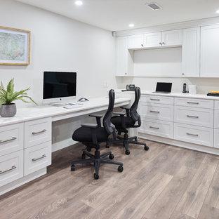 バンクーバーの中くらいのトランジショナルスタイルのおしゃれな書斎 (白い壁、ラミネートの床、造り付け机、茶色い床) の写真