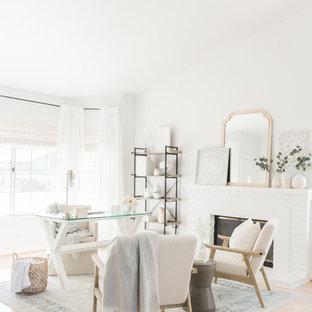 Ejemplo de despacho romántico, de tamaño medio, con paredes blancas, suelo de madera clara, chimenea tradicional, marco de chimenea de ladrillo, escritorio independiente y suelo beige