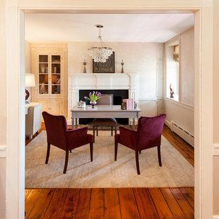 フィラデルフィアの中サイズのカントリー風おしゃれな書斎 (ベージュの壁、無垢フローリング、自立型机、標準型暖炉、石材の暖炉まわり、茶色い床) の写真