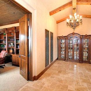 サンディエゴの広い地中海スタイルのおしゃれな書斎 (ベージュの壁、トラバーチンの床、自立型机、ベージュの床、暖炉なし) の写真