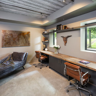 Design ideas for a small modern home office and library in Minneapolis with beige walls, concrete flooring and a built-in desk.