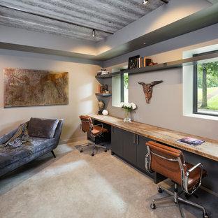 Inredning av ett modernt litet arbetsrum, med beige väggar, betonggolv och ett inbyggt skrivbord