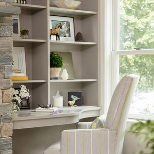 Immagine di un piccolo ufficio classico con pareti beige, parquet scuro, camino classico, cornice del camino in pietra, scrivania incassata e pavimento beige