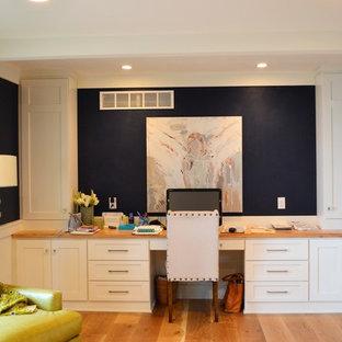 Ispirazione per un grande studio design con pareti blu, pavimento in legno massello medio, camino classico, cornice del camino in mattoni e scrivania incassata